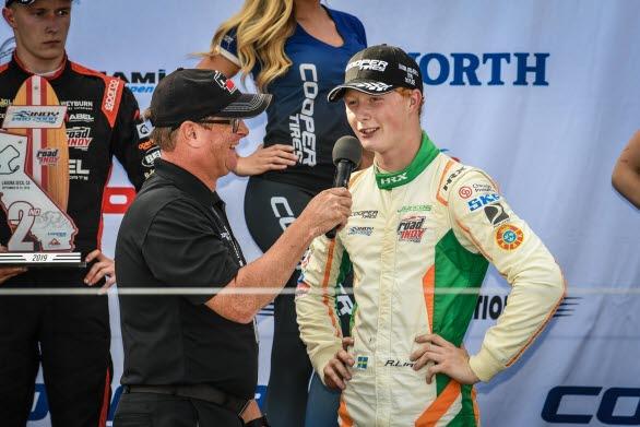 Rasmus Lindh från Kullavik intervjuas på podiet efter sin seger på Laguna Seca i Kalifornien. Kommande helg byter han sin Indy Pro 2000 formelbil mot en Porsche 911 GT3 Cup och startar i Carrera Cup-finalen på Mantorp Park.