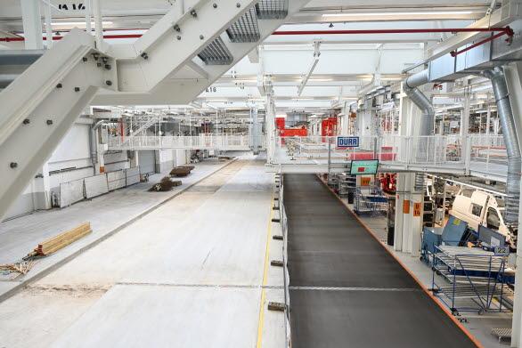 Till vänster monteras gamla maskiner ner för att göra plats för produktionen av nya ID. BUZZ. Till höger rullar bandet vidare med T6.1.